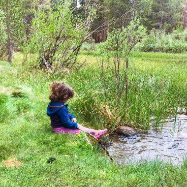 GIrl sitting at edge of creek.